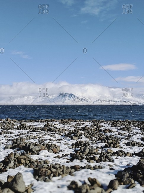 Stony beach along the reykjavik waterfront overlooking the bay and mountains, iceland
