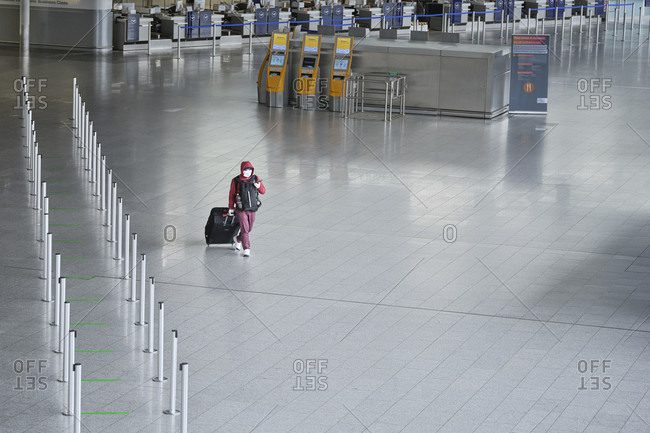 April 18, 2020: a masked traveler crosses terminal 1 at frankfurt airport during the general lockdown in Germany due to the corona pandemic.