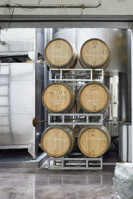 December 20, 2016: wine barrel cellar with barrique barrels in shelving systems and chalk lettering according to grape variety or location, in front of stainless steel wine tanks