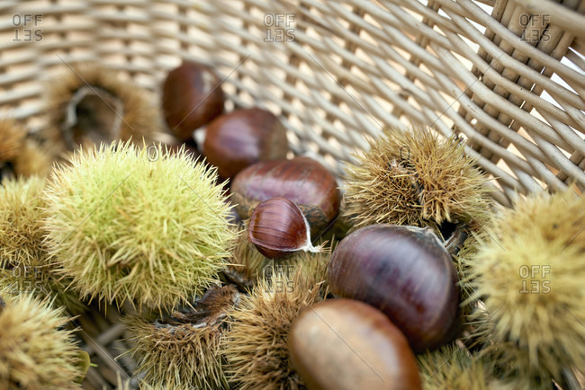 Sweet chestnuts with and without shell in a small basket