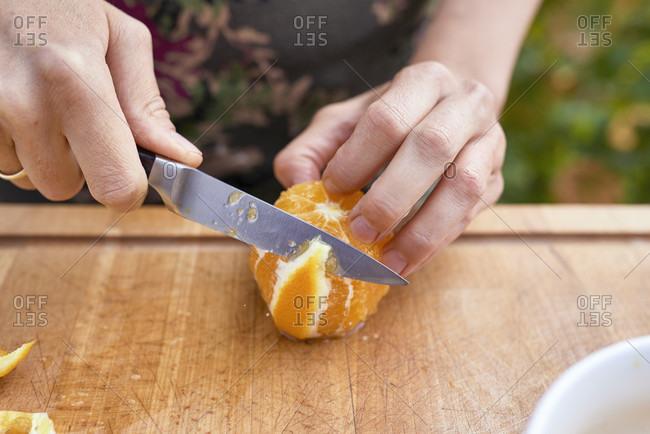 Female hands fillet orange on wooden board