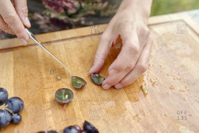 Women's hands with a kitchen knife stone grapes