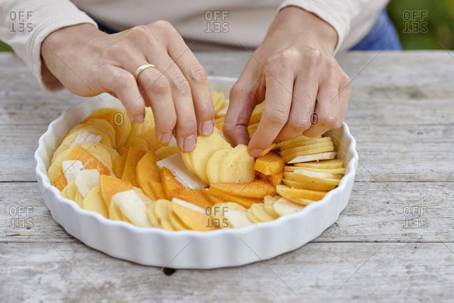 Prepare a gratin of potatoes, pumpkin and jerusalem artichoke, arrange the sliced ingredients in a buttered baking pan