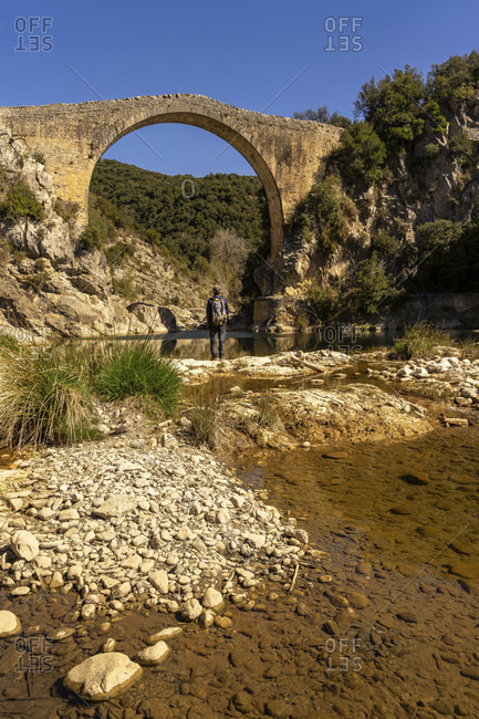 Europe, Spain, catalonia, gerona province, la garrotxa, montagut, hiker looks at the medieval bridge over the llierca river