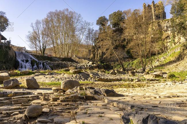 Europe, Spain, catalonia, gerona province, la garrotxa, sant joan les fonts, view of the salt del molí fondo waterfall and the church in sant joan les fonts