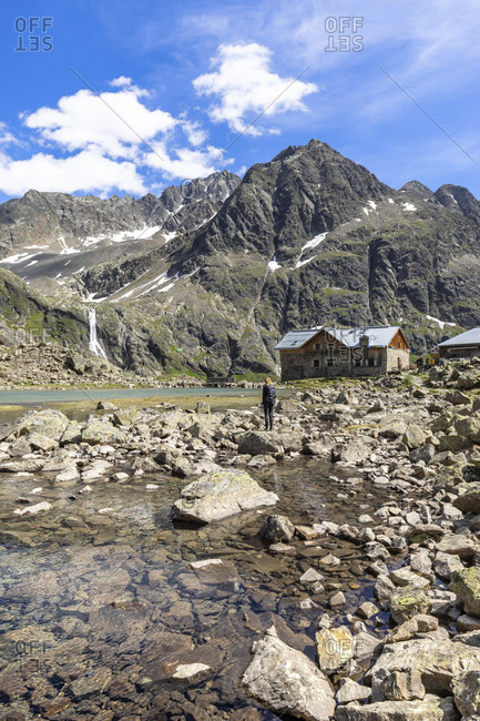 Europe, austria, tyrol, otztal alps, otztal, gries im sulztal, mountain hiker stands at winnebachsee in front of the winnebachseehutte in sellrain
