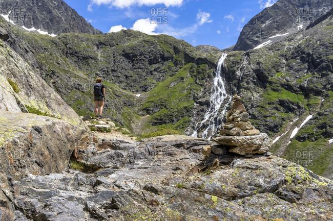Europe, austria, tyrol, otztal alps, otztal, gries im sulztal, mountain hiker looks at the waterfall at the winnebachseehutte
