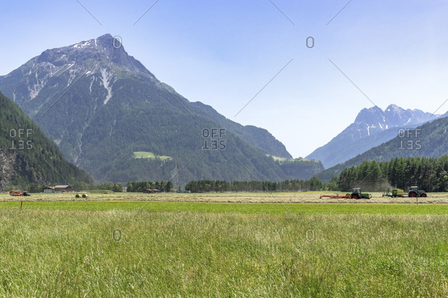 Europe, austria, tyrol, otztal alps, otztal, combine harvester on a meadow with the gamskogel in the background