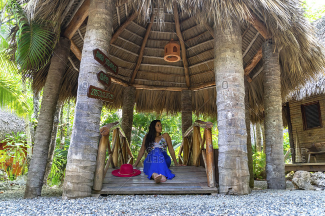 America, caribbean, greater antilles, dominican republic, cabarete, woman sitting on a small wooden bridge in the natura cabana boutique hotel & spa