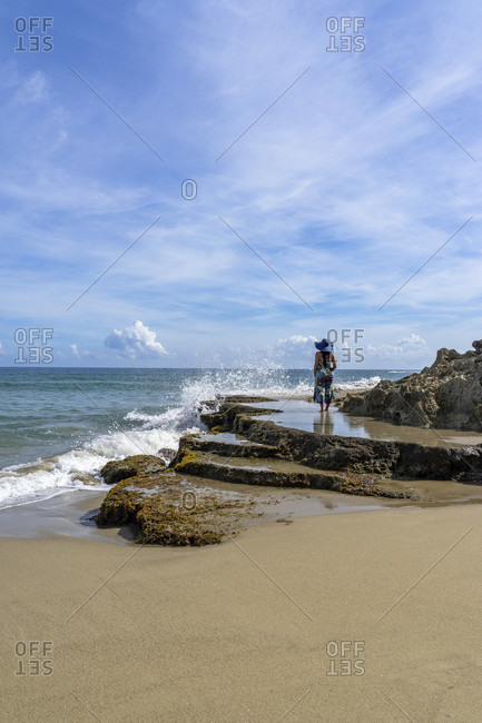 America, caribbean, greater antilles, dominican republic, cabarete, woman stands on a rock and looks out to sea