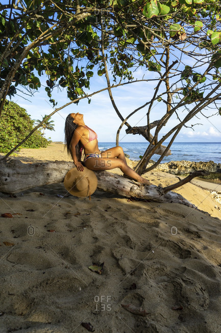 America, caribbean, greater antilles, dominican republic, cabarete, woman sitting on a log on the beach of the natura cabana boutique hotel & spa