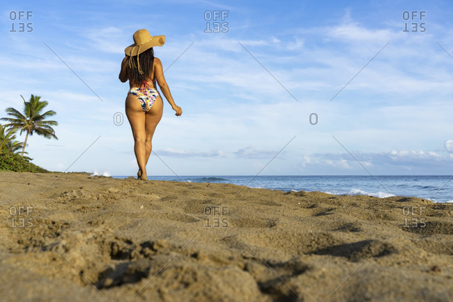 America, caribbean, greater antilles, dominican republic, cabarete, woman strolls along the beach of the natura cabana boutique hotel & spa