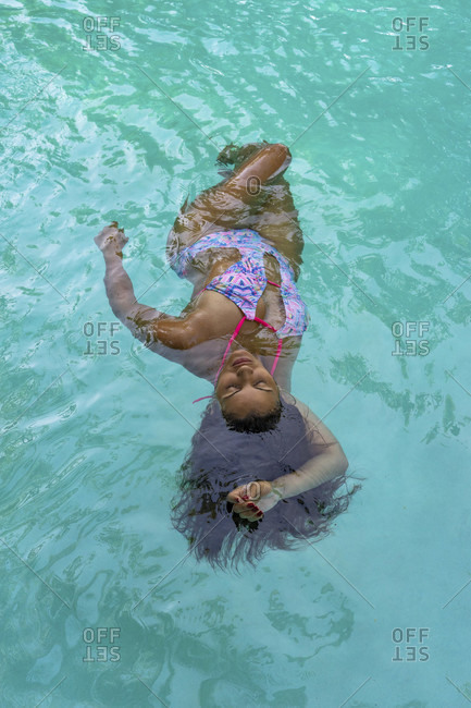 America, caribbean, greater antilles, dominican republic, cabarete, woman swims on her back in the pool of the natura cabana boutique hotel & spa