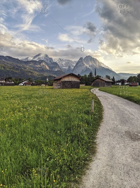 Path leads along a spring meadow with a view of the zugspitze massif and 2 church towers in garmisch-partenkirchen