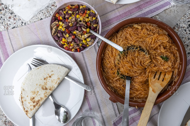 Above photograph of a table served with vegetarian food with mexican-style noodle pasta accompanied by beans and quesadillas