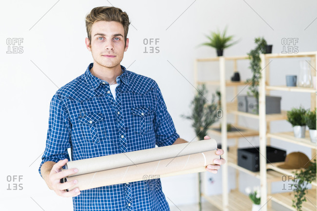 Young man holding blueprint tube while standing at office