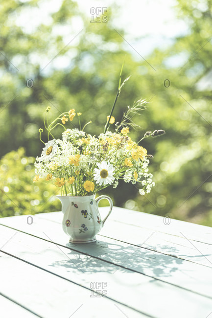 Spring - The garden blooms in the sunlight. Daisies and buttercups in a vase in the garden.