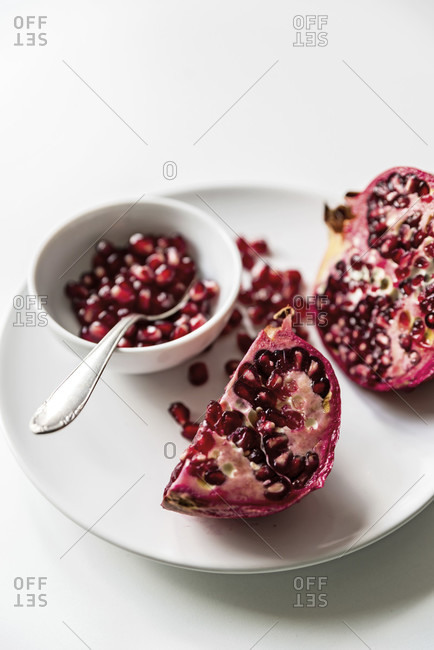 Sliced red pomegranate on white plate and white background, loose kernels in white bowl with silver spoon