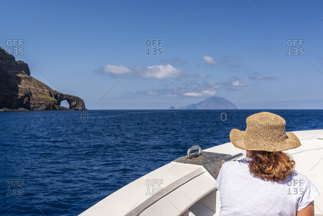 Sicily - Sunny impressions of the Aeolian Islands, woman with a straw hat enjoys the boat trip from Salina towards Filicudi.