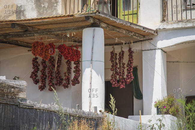 Sicily - Sunny impressions of the Aeolian Islands, Onions and vine tomatoes hang in a courtyard to dry. Salina.