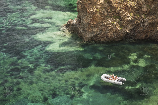 Sicily - Sunny impressions of the Aeolian Islands, crystal clear water at Cala Junco, Panarea, couple in an inflatable boat.