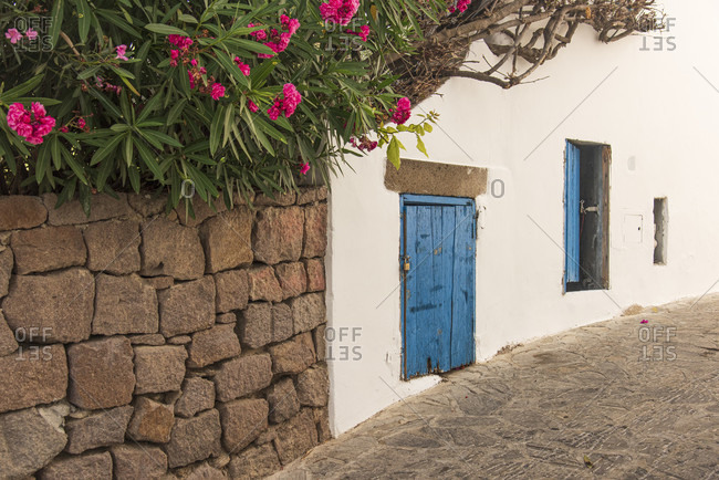 Sicily - Sunny impressions of the Aeolian Islands, Blue wooden doors and oleanders on the roadside in Panarea.