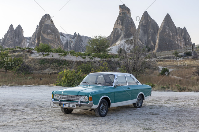 September 27, 2019: Ford Taunus in front of the eroded landscape and rock towers near Goreme, Cappadocia, Anatolia, Turkey