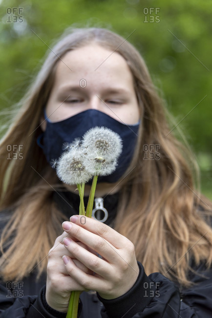 Schoolgirl with a mask holding several dandelions