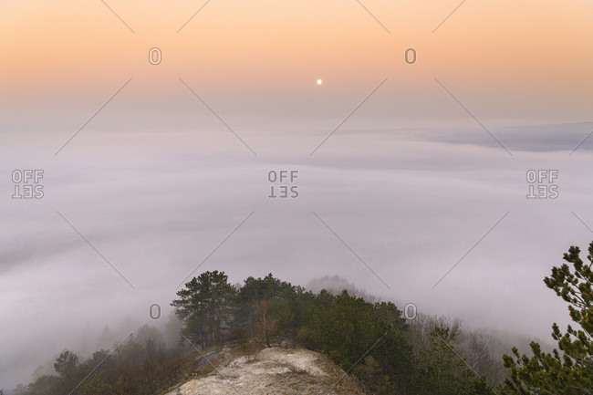 Moonset and sunrise over Jena in the morning mist