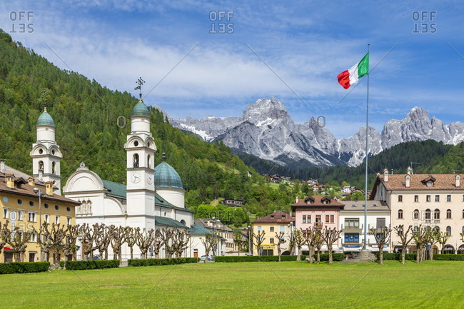 May 3, 2020: the center of Agordo with the church with two bell towers and the large green lawn called 'broi', agordino, belluno, veneto, italy