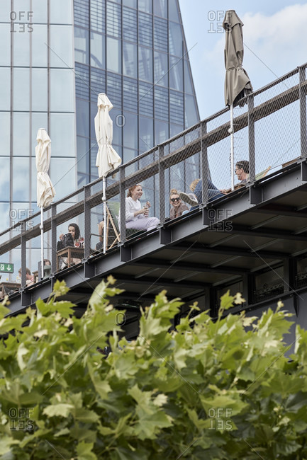 July 7, 2019: Guests on the observation deck of the Oosten excursion restaurant in Frankfurt's Ostend, in the background is the facade of the ECB.