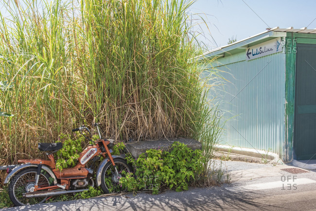 July 20, 2018: Sicily - Sunny impressions of the Aeolian Islands, also known as Aeolian Islands, old Rizzato Califfo moped on the roadside, Salina Island.