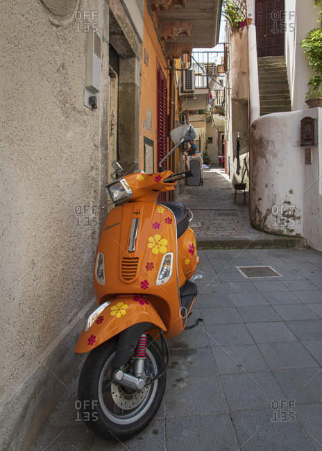 July 20, 2018: Sicily - Sunny impressions of the Aeolian Islands, also known as Aeolian Islands, flower power hippie style scooter in an alley in Lipari town.