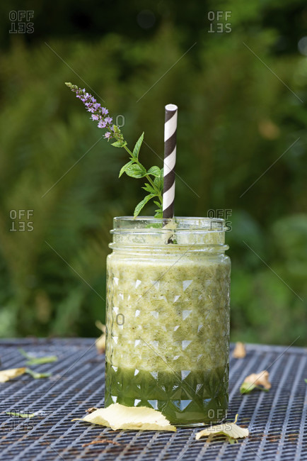 Green smoothie in a glass with straw and mint blossom stands on garden table, background blurred, green.