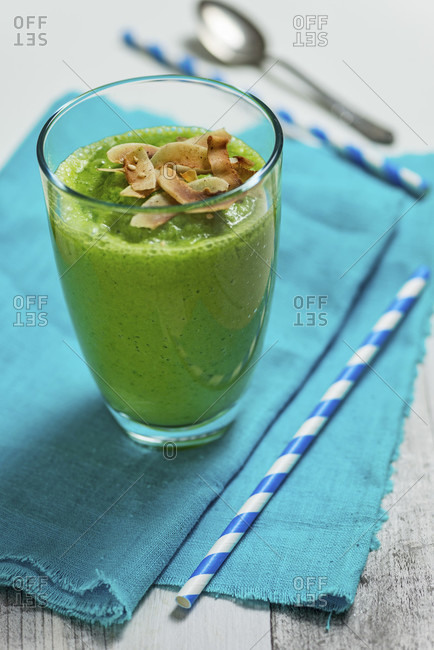 Green smoothie in a glass on a turquoise cloth with two blue and white straws and a silver spoon