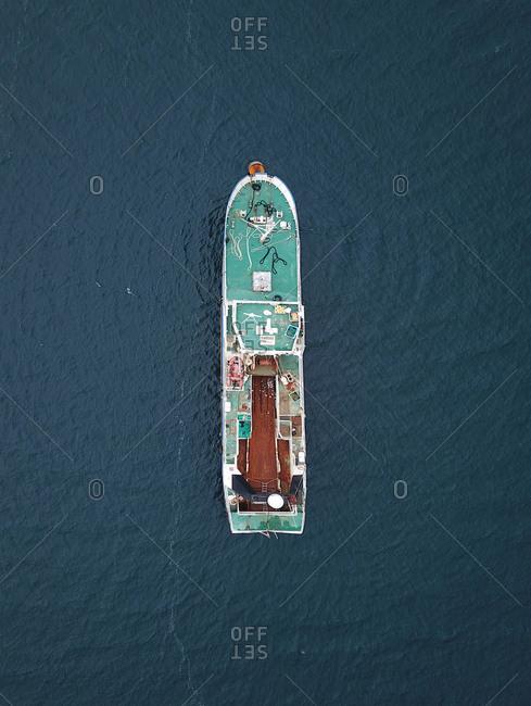 Aerial view of green fishing ship in the blue Atlantic ocean in Streymoy, Faroe Islands, Denmark.