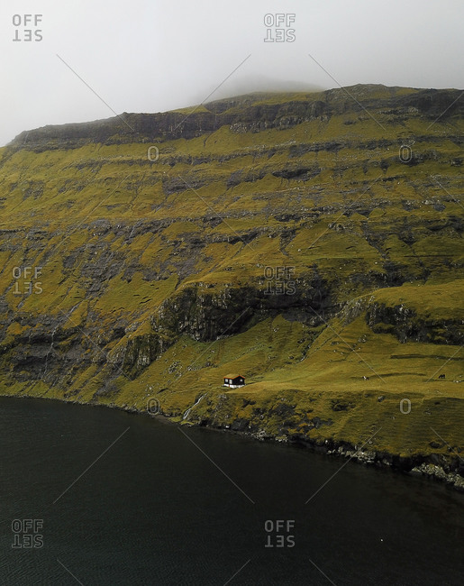 Aerial view of tiny colorful cabin next to waterfall and cliffs in foggy mountains in Saksun, Faroe Islands, Denmark.