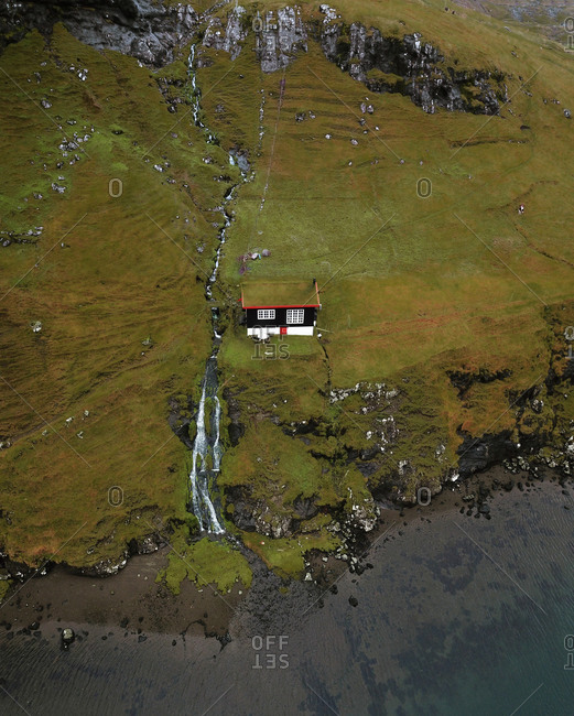Aerial view of tiny colorful cabin with grass roof next to waterfall and cliffs in foggy mountains in Saksun, Faroe Islands, Denmark.