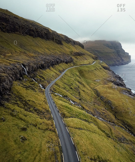 Aerial view of road over a waterfall in the foggy mountains leading to tiny town  in Faroe Islands, Denmark.