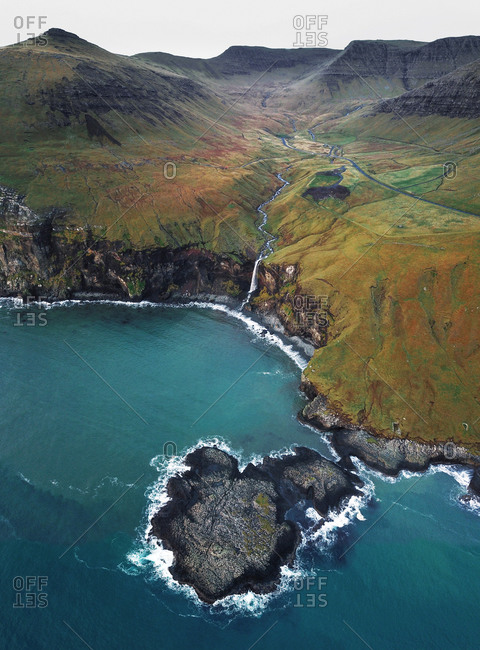 Aerial view of mountain waterfall  flowing into the Atlantic Ocean surrounded by mountains on in the Faroe Islands, Denmark