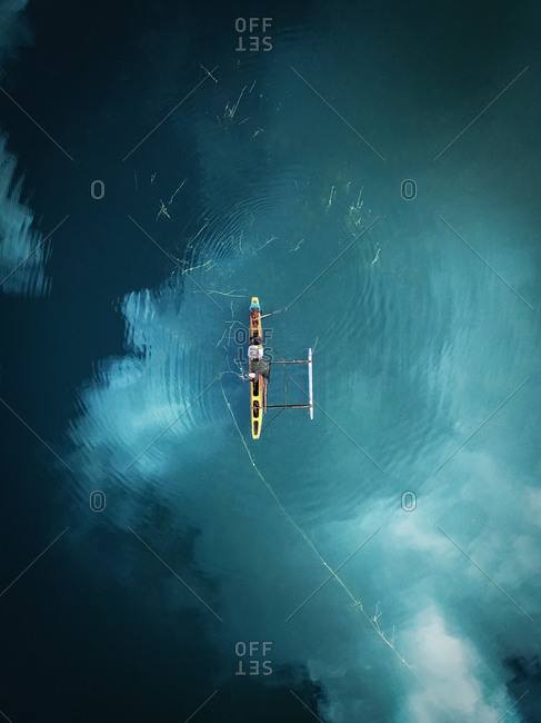 Aerial view of people fishing in traditional outrigger boat in lake with cloud reflections from above in Polonnaruwa, Sri Lanka