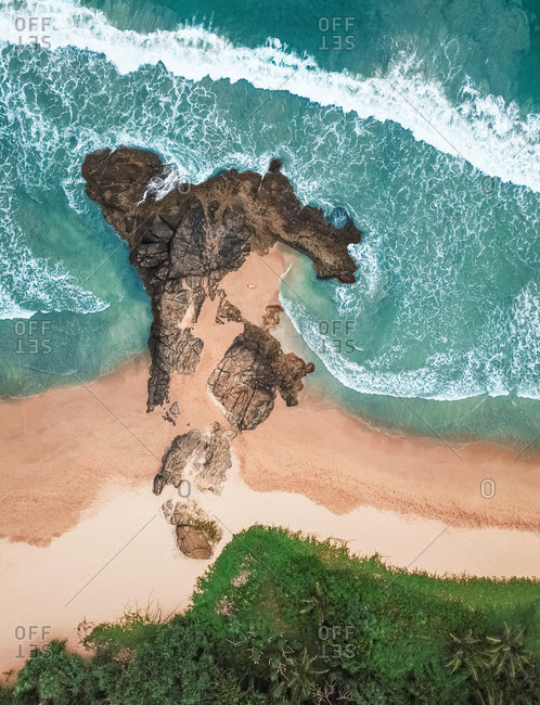 Aerial view of girl lying on rocky private beach by the ocean with waves crashing in Bentota, Sri Lanka