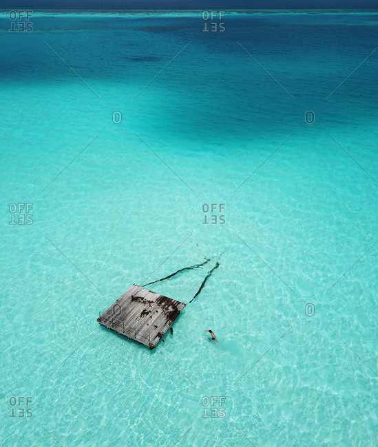 Aerial view of person swimming to Pontoon in the crystal clear blue turquoise ocean in the tropical paradise Maldives, Indian Ocean