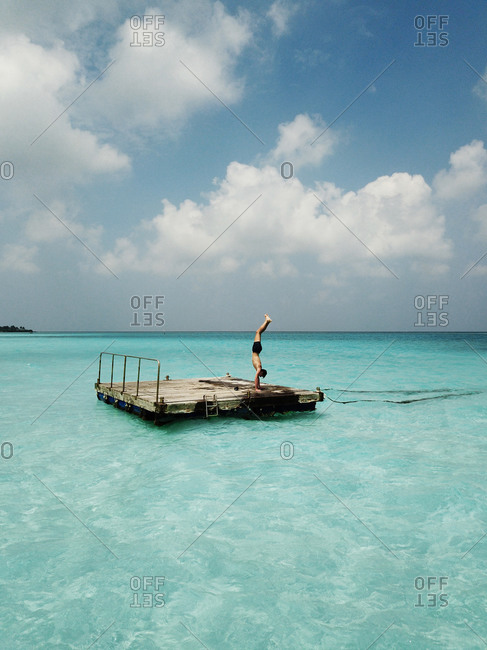 Aerial view of man doing a handstand on a Pontoon in the crystal clear blue turquoise ocean in the tropical paradise Maldives, Indian Ocean.