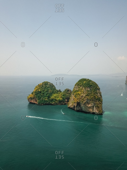 Aerial view of tiny speed boats exploring the giant limestone cliffs and islands in the turquoise blue sea, a tropical paradise, Phra Nang, Krabi, Phuket, Thailand.