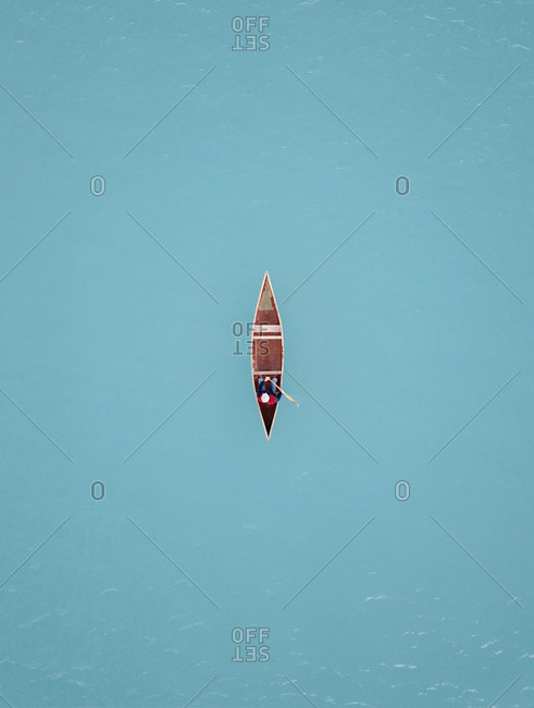 Aerial view of a classic Canadian canoe paddling on glacial turquoise blue Lake Tekapo, South Island, New Zealand