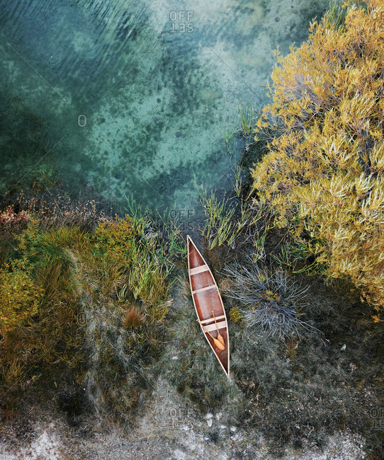 Aerial view of classic Canadian canoe paddling on small pond lake with reeds and bushes in Tekapo, South Island, New Zealand