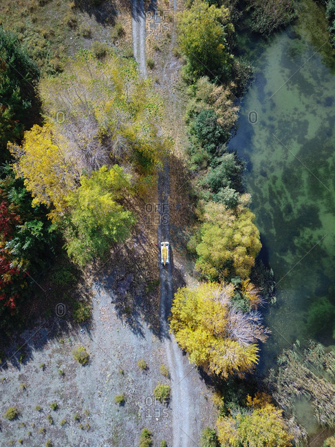 Aerial view of van with canoe driving on dirt track surrounded by lakes and autumn color trees in Tekapo, South Island, New Zealand