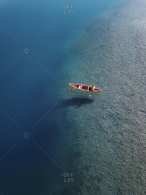 Aerial view of a person paddling Canadian canoe into deep crystal clear water with boat shadow on Lake Wakitipu, South Island, New Zealand