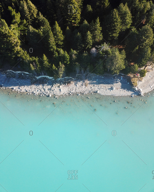 Aerial view of evergreen trees and turquoise blue glacial water at the edge of Lake Pukaki, South Island, New Zealand
